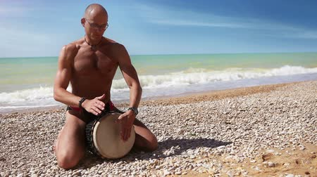 loud music : Djembe traditional Drum Player beat rythm on the lonely beach