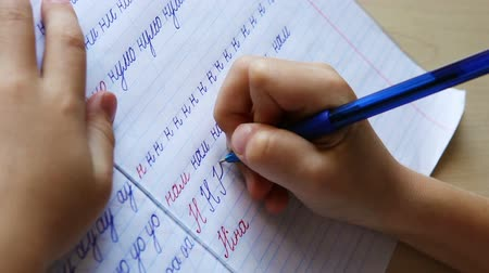 домашнее задание : First steps in writing: little boy writes russian N letter in diagonal lined notebook