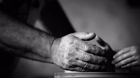 alkotás : Hands of old potter and young follower