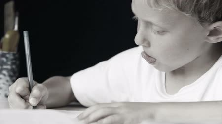 autor : Little boy diligently writes his homework: black and white style