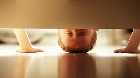 alatt : Cheerful little boy look under the bed and sincerely smiling