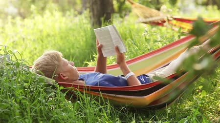 гамак : Reading last bestseller in cosy Hammock in apple trees shadows Стоковые видеозаписи