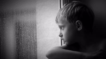 Łzy : Alone little boy looks raindrops through window glass Wideo