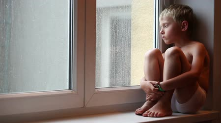 lonely : Alone little boy looks raindrops through window glass Stock Footage