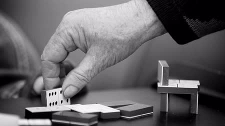casas : Old pensioner woman builds a construction with dominoes concept