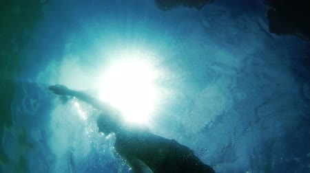 jasno : Swimming men silhouette with sun rays from bottom camera Dostupné videozáznamy