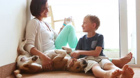 kobieta pies : Happy mother and son family on the home floor with friendly beagle dog