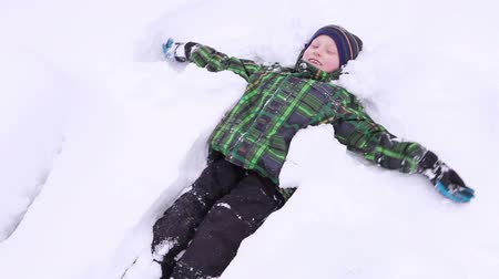 snow angel : Little boy smiling and doing Snow angel