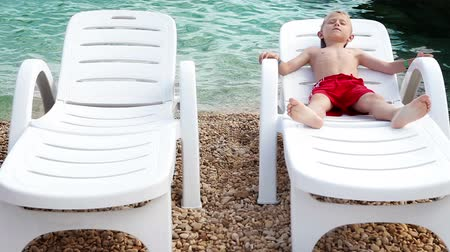 стулья : Little boy tans on the sea coastline in white deck chair Стоковые видеозаписи