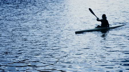 kayak : A silhouette of a person rowing a canoe  High Definition Video : 23.97 FPS 20sec   Please look another footages with professional demo Exercises  on my TrainArrival Account.     Best Wishes. Stock Footage