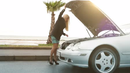 sıkıntı : Pretty blonde girl looking something under the hood of her broken car Stok Video