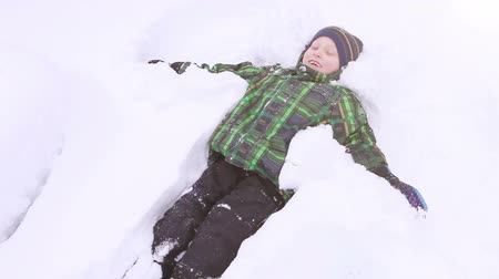 snow angel : Accelerated footage: Little boy covering himself with snow doing angel figure  High Definition Video : 29.97 FPS 7sec Please look another footages on my TrainArrival Account.  Best Wishes. Stock Footage
