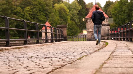 macskaköves : A man is walking along the old cobbled dam in Liberec, Czech Republic in autumn time  High Definition Video : 23.98 FPS 8sec   Please look another footages on my TrainArrival Account.     Best Wishes
