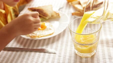 scrambled eggs : Mother pouring orange juice his little son during morning fried eggs breakfast