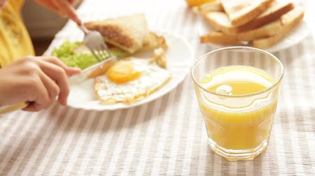 scrambled eggs : Hungry little pupil cuts his fried eggs during the breakfast - orange juice flounders about in the glass as he does it  High Definition Video : 29.97 FPS 9sec Please look another footages on my TrainArrival Account.  Best Wishes.