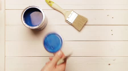 oak wood : A carpenter prepares his working place: opens up a tin with blue paint