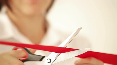 unveil : Business woman cutting the red ribbon with scissors and open the event