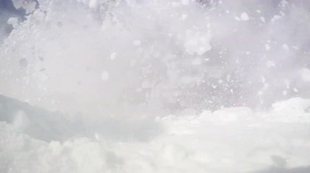 sporty zimowe : Slow-motion dynamic footage of a skier going down the slope : snow flies into the camera