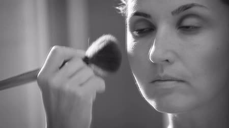 greasepaint : Black and white footage: young woman prepares for game day at work applying make-up