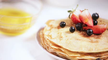 placas : Honey pouring on the fresh cooked pancakes with blueberries and strawberries