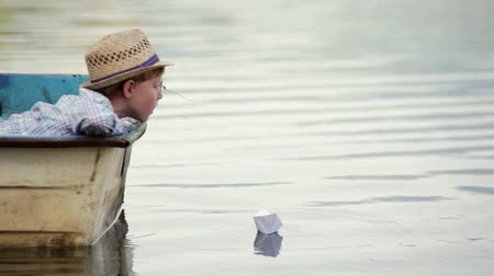 наслаждаясь : Boy wearing wicker hat sitting in the boat setting his paper boat on a journey  High Definition Video : 29.97 FPS 17sec   Please look another footages   on my Train_Arrival Account.     Best Wishes. Стоковые видеозаписи