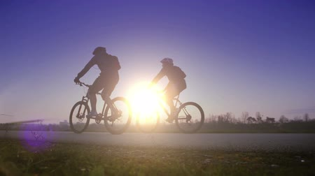 večer : Bright saturated footage of two cyclists riding in one direction at sunset  High Definition Video : 29.97 FPS 10sec   Please look another footages on my Train_Arrival Account.  Best Wishes.