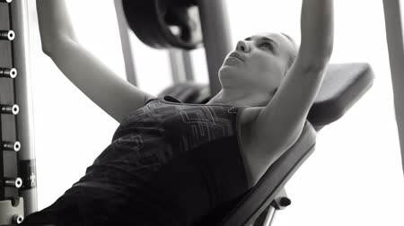 eğitici : Black and white footage of a lady working out in the gym lifting the barbell  High Definition Video : 29.97 FPS  19sec Please look another footages on my Train_Arrival Account.  Best Wishes.