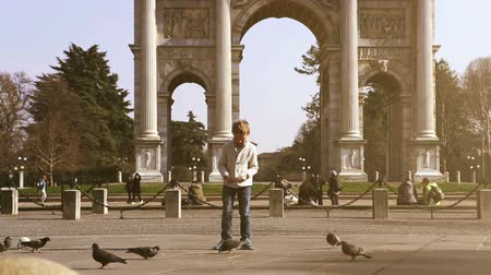 arco : Little boy feeding the pigeons on the Sempione Square in Milan with Porta Sempio Stock Footage