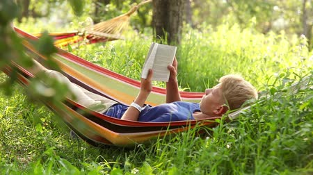 гамак : Man reading the book in cozy hammock under the trees shadows