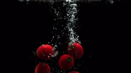 horeca : Fresh ripe tomatoes falling into clean water with air bubbles and droplets on black background