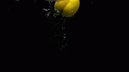 horeca : Fresh vegetable yellow bell pepper falling into water with lot of air bubbles