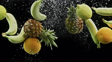 fructose : Fresh tropical fruits pineapple oranges lemons and banana falling into water on black background