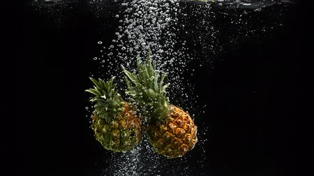 fructose : Tropical fruits pineapple falling into water with splash and air bubbles on black background Stock Footage