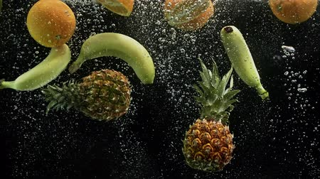 fructose : Tropical fruits pineapple oranges and banana falling into water on black background Stock Footage
