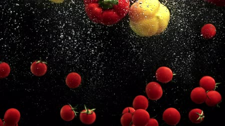 horeca : Cherry tomatoes and red yellow paprika bell peppers falling into water with air bubbles black background