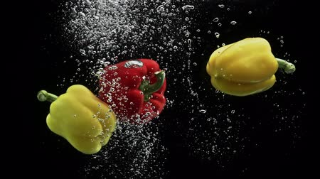 horeca : Red and yellow pepper falling into water and spinning air bubbles on black background Stock Footage