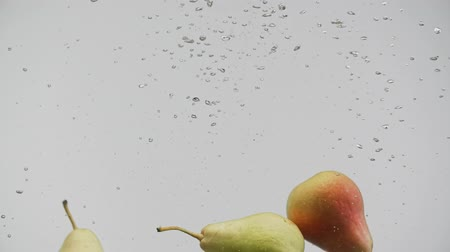 fructose : Fresh fruits red yellow pears falling water splash air bubbles white background