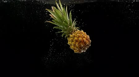 fructose : Tropical fruit pineapple falling in water splash air bubbles black background