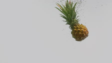 fructose : Pineapple tropical fruit falling into water with splash and air bubbles