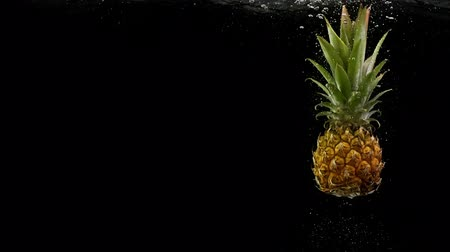 fructose : Tropical fruit pineapple under water with splash and air bubbles on black