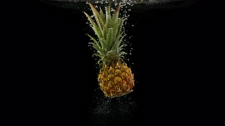 fructose : Tropical fruit pineapple falling into water on black background Stock Footage