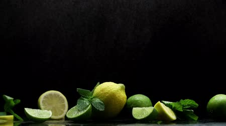 cítrico : Fresh lemon and lime cuts under cold drops of fog and water black background