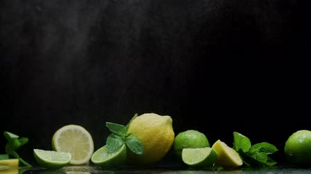 cítrico : Fresh lemon and lime cuts under cold water spray fog on black background