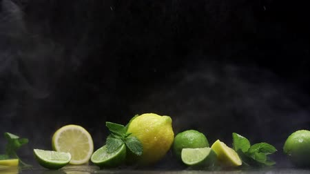 cítrico : Fresh lemon and lime cuts under cold water spray and ice fog on black background
