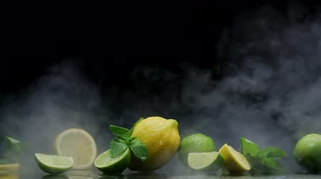 cítrico : Lemon and lime cuts in cold ice clouds of fog on black background