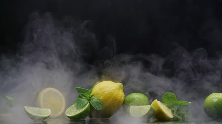 cítrico : Lemon and lime cuts in cold ice clouds of fog under water spray drops on black background