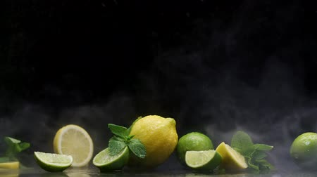 sitrik : Tropical lemon lime cuts in cold ice clouds of fog under water spray droplets black background