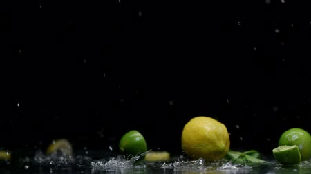 calcário : Tropical lemon and lime cuts under water splash with lot of drops on black background Stock Footage
