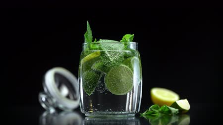 цитрусовые : Citrus mojito lemonade with lime lemon and mint in cold sparkling water prepared for drinking Стоковые видеозаписи