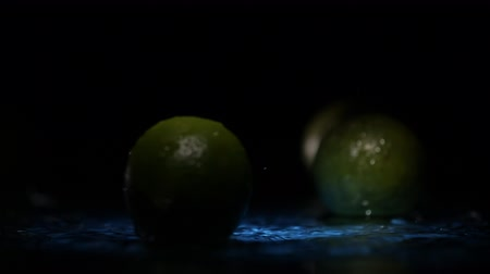 ferahlatıcı : Close-up of lime fruits falling on water surface in blue light spot with liquid splash and drops in slow motion